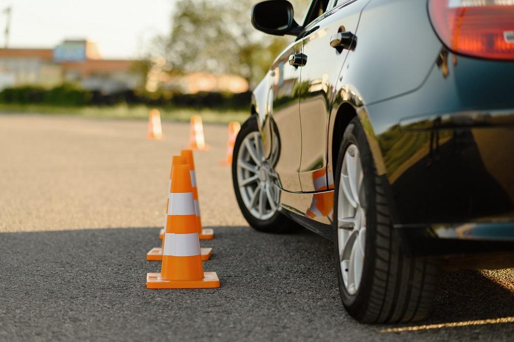 車が三角コーンの横を走っている写真
